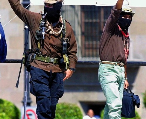 """Mexican rebel leader """"Subcomandante Marcos"""" (L) and comandante Tacho (R) wave to the massive crowd from a podium set up in front of the presidential palace 11 March 2001 in the Mexican capital. The rally, with an estimated 150,000 people, marked the conclusion of a two-week, 3,000-kilometer (1,900-mile) drive from the jungles of Chiapas, led by Marcos and 24 rebel commanders, with the participation of hundreds of supporters.  AFP PHOTO/Jorge UZON        (Photo credit should read JORGE UZON/AFP/Getty Images)"""