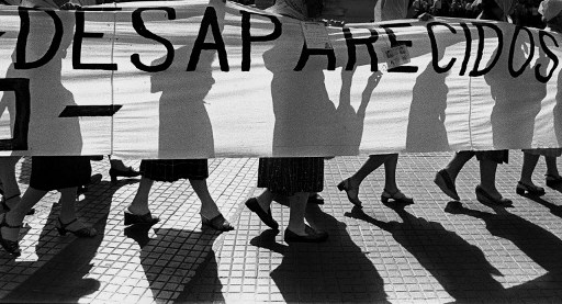 """(FILE) Members of the """"Madres de Plaza de Mayo"""" human rights organization, hold a banner claiming for their missing sons and daughters as they walk in front of the Presidential Palace, circa 1980 in Buenos Aires. The organization will be 30 years next April 30th, 2007. According to human rights organizations about 30.000 people disappeared in Argentina during the military dictatorship, 1976-1983. """"Madres de Plaza de Mayo"""" members still walk in Plaza de Mayo every Thursday. AFP PHOTO/Daniel GARCIA / AFP PHOTO / AFP FILE / DANIEL GARCIA"""